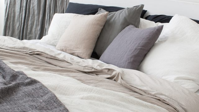 Bed with white and grey linens and a lot of pillows.