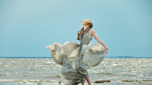 A woman dances in a silk dress on a beach