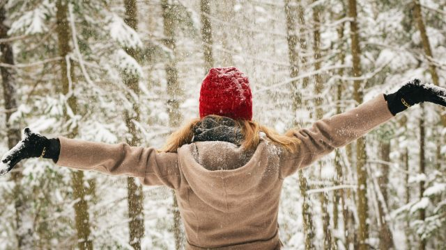 Woman with outstretched arms in a wooded winter environment