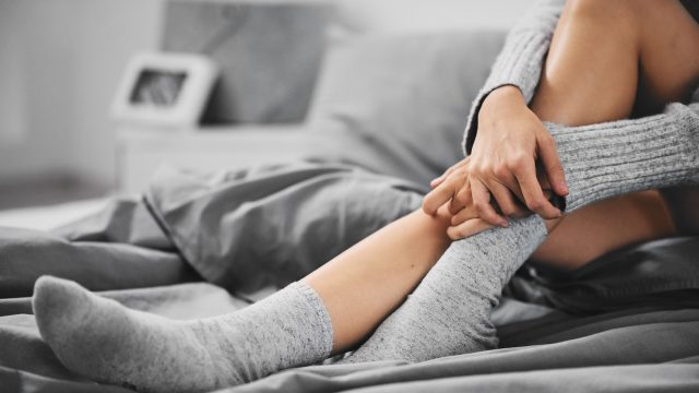 A woman wearing silk socks on a bed