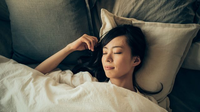 woman laying in a bed with a silk pillowcase and bedding