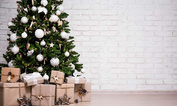 decorated christmas tree and gift boxes over white brick wall