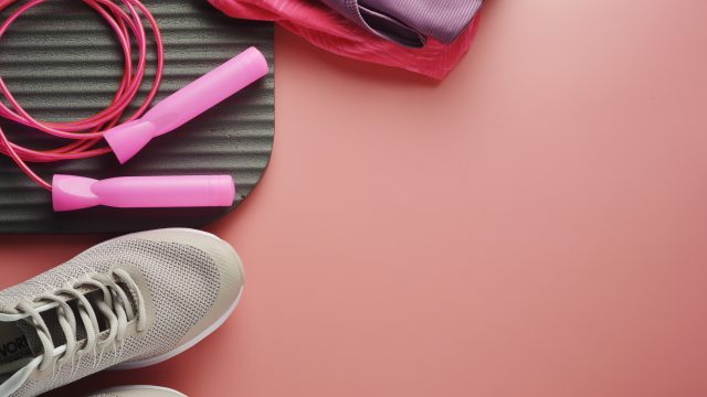 Workout. Sport shoes, jumping rope, yoga clothes over pink background. Health, running workout, fitness and yoga concept.