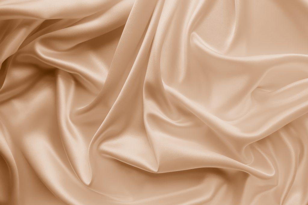 Beautiful smooth elegant wavy beige / light brown satin silk luxury cloth fabric.