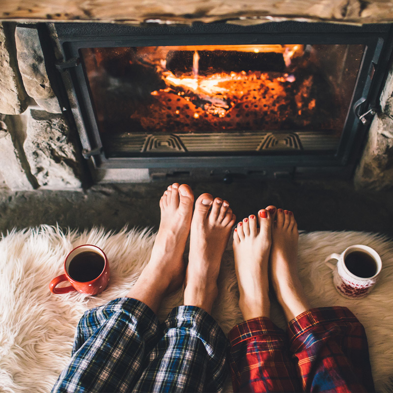 A man and woman in their pyjamas sat in front of the fire with a hot drink.