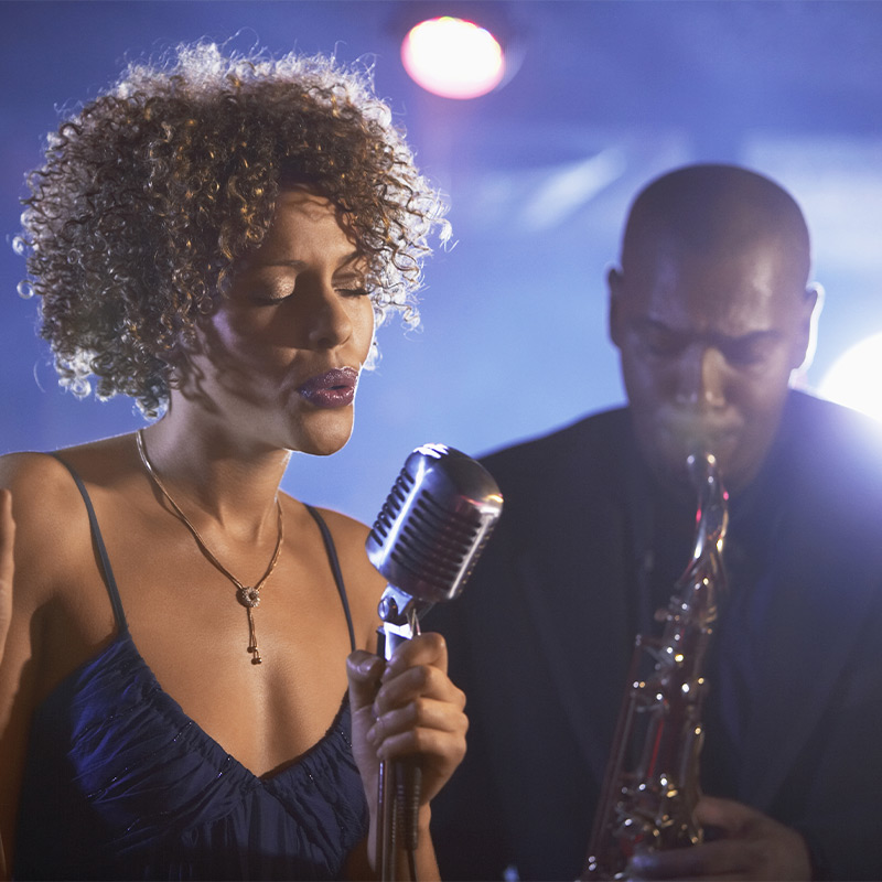 A woman singing into a microphone and a man behind her playing the saxophone.