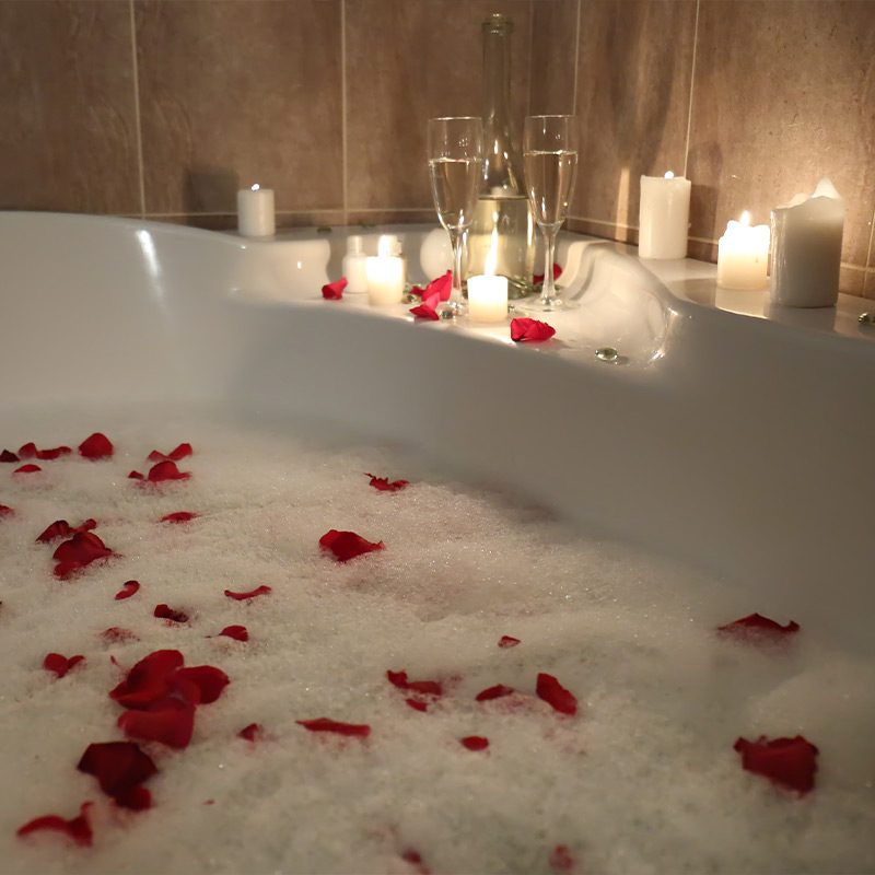 Bath filled with soapy water and rose petals. Candles lit next to the bath with 2 glasses of bubbly.
