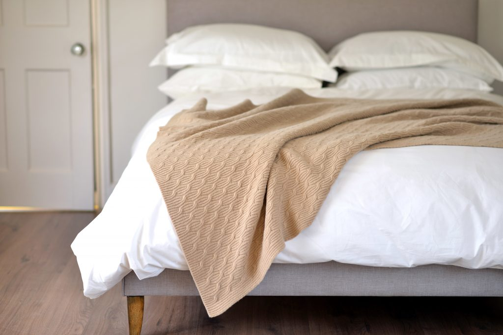 Bedroom setting with luxury pillows, shams and duvets. Sheet draped over the edge of the bed.