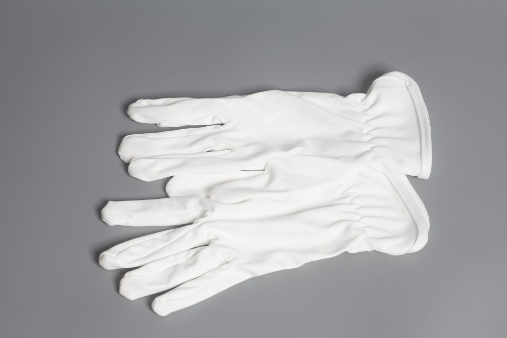 White service gloves laid out on a grey background.