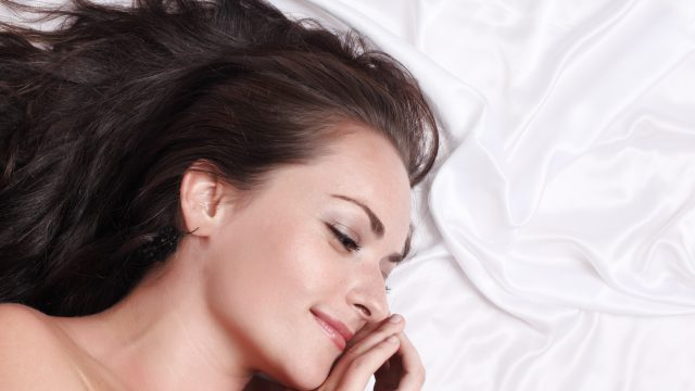 Portrait of beautiful happy woman lying on white silk bed